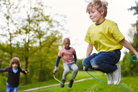 Boy in the park together with friends in competition in rope skipping in summer 版權商用圖片 - 116338415