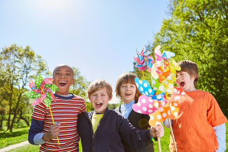 Multicultural children group in summer camp with colorful windmill Stock Photo