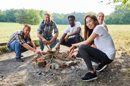 Multicultural group of young people collects firewood in Survival Training Workshop