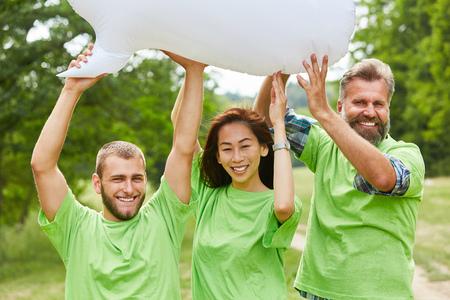 Trois militants tiennent un ballon blanc ensemble dans la nature Banque d'images