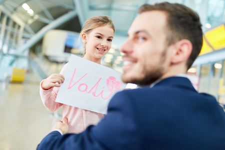 Father is picked up by daughter at the airport terminal and greeted with a sign featuring the German word