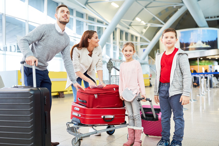 Family and two children with luggage are flying on vacation and standing in the airport terminal