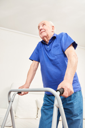 Senior learns to walk again with walker in occupational therapy in rehab