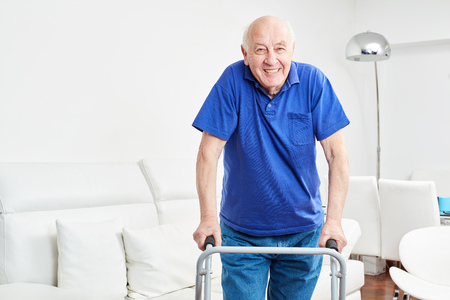 Senior in rehab learns walking with walker and smiles optimistically Stock Photo