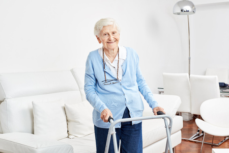 Smiling old woman with walker is learning to walk in her apartment in rehab