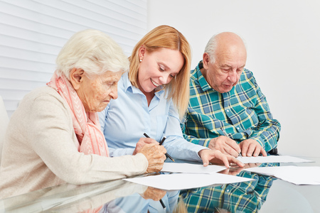 Woman advises senior couple on tax and finance with home documents