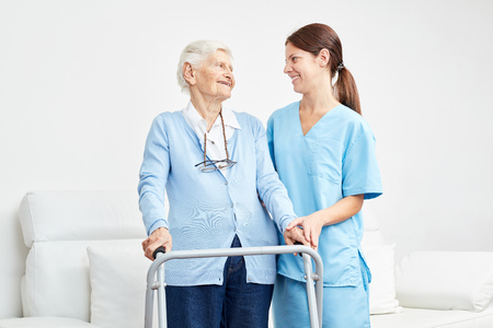 Old woman learns to walk with a walker and is supported by caregiver