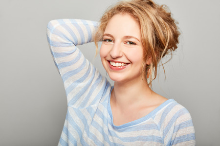 Young laughing blond woman holds up her hair
