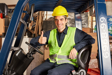 Young warehouse worker with thumbs up as a stacker driver in a warehouse