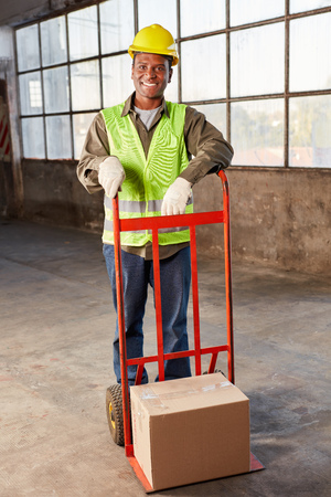 Young logistics worker carries a package on hand truck by mail order