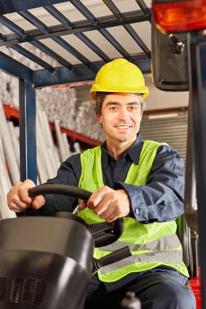 Smiling warehouse worker as a forklift driver transports freight in shipment Banque d'images