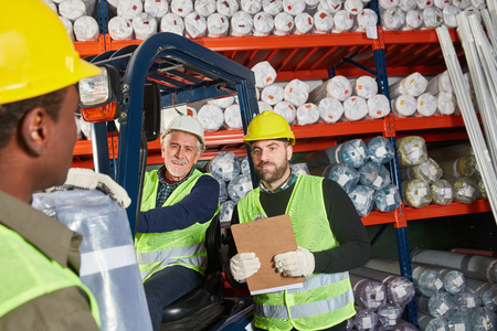 Workers as a logistics team in the carpet warehouse work together in shipping