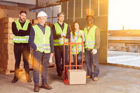 Happy warehouse worker group as a team in warehouse by a mail order company