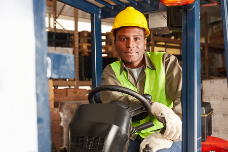 Young man as apprentice on the forklift in the warehouse in a warehouse
