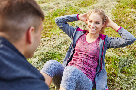 Man helps woman with sit-ups after power training