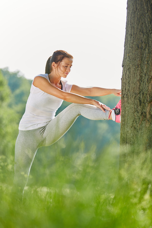 Young woman stretching on tree before running in the park