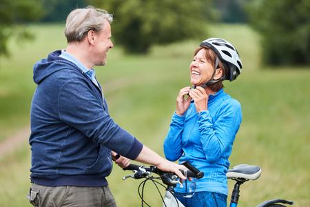 Une femme âgée active met un casque de vélo avec son partenaire avant la balade à vélo