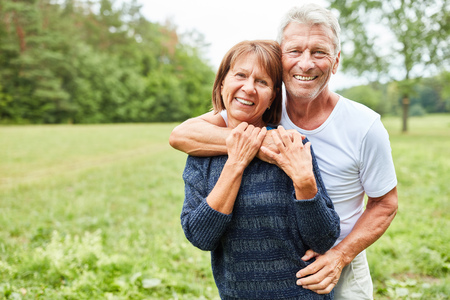 Happy senior couple hugging each other in love on a meadow in the park