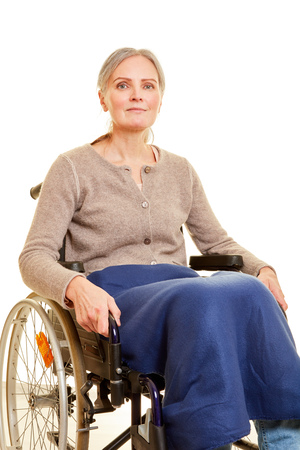 Smiling elderly woman is sitting in wheelchair