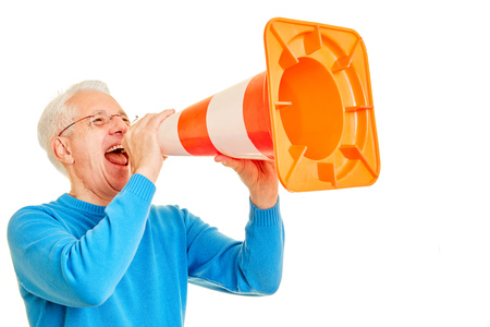 Old angry man uses pylon as a megaphone for communication