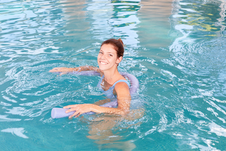 Young woman in swimming pool doing aqua gymnastics for fitness and health