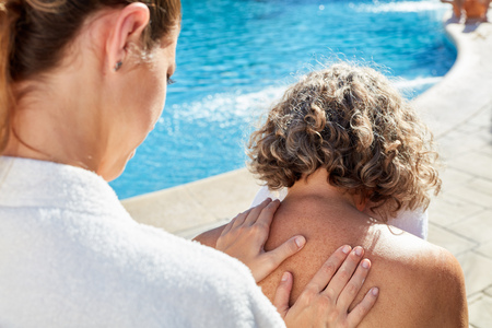 Physiotherapist massaging the back of a senior woman at the pool in the spa hotel