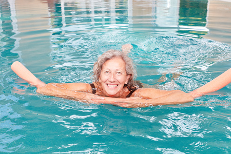 Happy senior woman with swimming aid at aquafitness and hydrotherapy