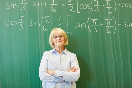 Senior woman as math teacher or lecturer in front of chalkboard