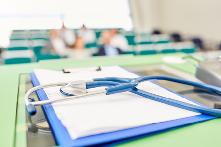 Stethoscope and clipboard on speaker desk in medicine training lecture Stock fotó