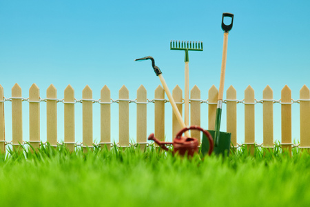 Gardening tool at the fence from the garden on a green meadow in spring