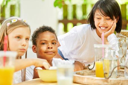 Multicultural group of children has breakfast together in kindergarten