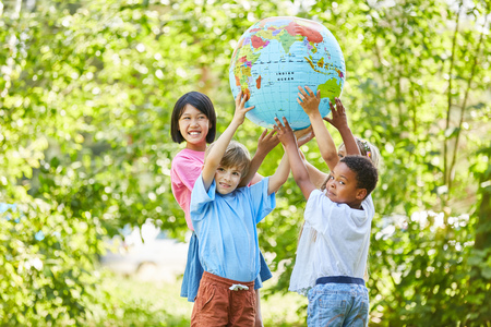 International children group as a team holds a globe in nature Foto de archivo