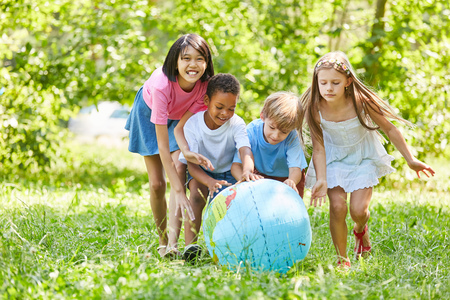 Children in the International Kindergarten are rolling a globe together Stockfoto