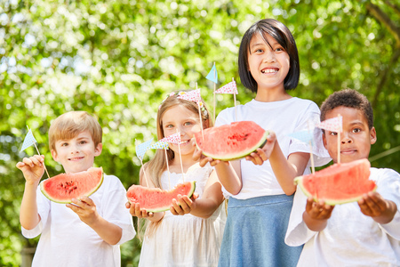 Multicultural group of kids serving fresh watermelons as a party snack