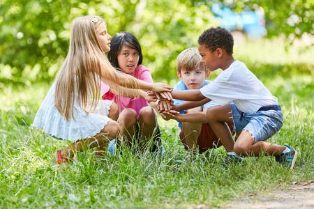 Multiculturele groep kinderen stapelt handen op als teken van vriendschap Stockfoto