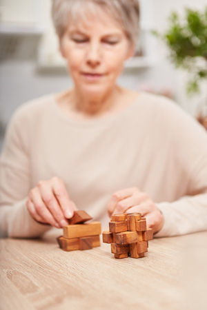 Senior woman citizen with dementia building blocks and playing