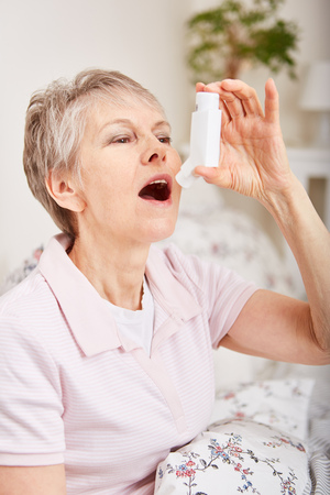 Senior woman with asthma using inhaler
