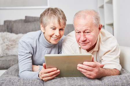 Senior couple with tablet computer surf the web with curiosity