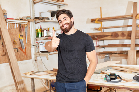 Young man as start-up founder keeps his thumbs up in the joiner's workshop