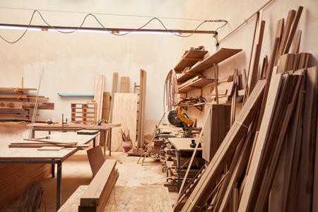 Pusty warsztat w stolarni z magazynem drewna i stołem warsztatowym