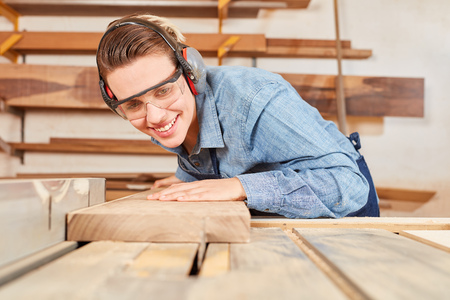 Young woman as joiner trainee works with wood on a circular saw in the joinery Stok Fotoğraf