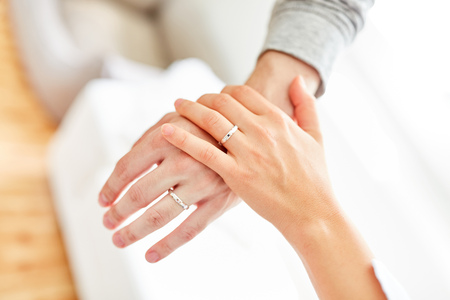Female and male hand with wedding rings on ring finger touch each other