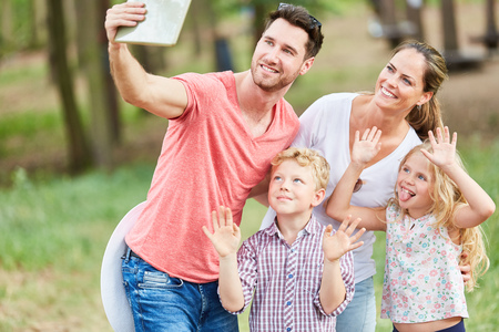 Family with children takes a selfie photo on vacation in the summer in nature