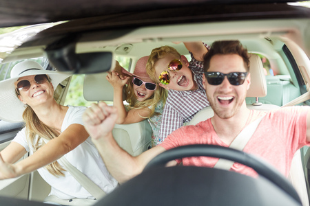 Cheerful family with sunglasses is singing together in the car on the trip