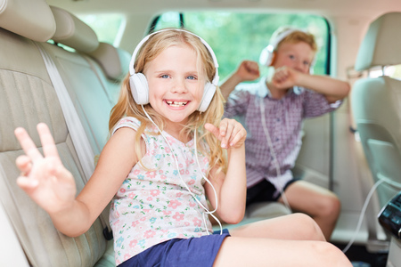 Happy siblings. Children listen to music on headphones in the car and sing to it