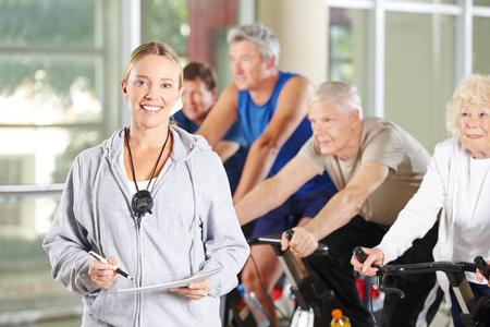 Woman with stopwatch and training plan as a trainer for seniors in the fitness center