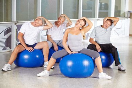 Group of seniors stretching neck at rehabilitation sport in fitness center