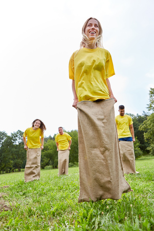 Young sporty woman with her team makes sack races at a competition