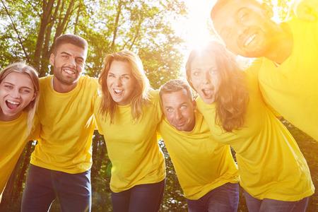 Lachende groep als team in knuffel tot motivatie in de natuur