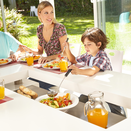 Child takes salad with trowel at the table at lunch in the circle of family